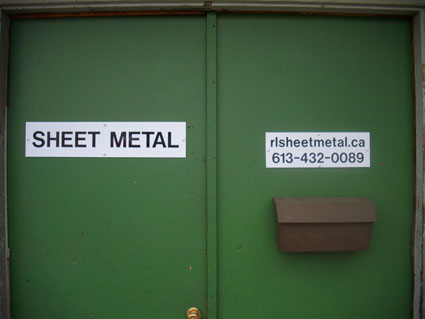 Photo of the shop door with contact information